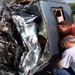 """Emergency responders peer into a damaged vehicle. Rev. Patrick Dowling revealed himself as the mysterious """"angel priest"""" who prayed with 19-year-old Katie Lentz, after reading a National Catholic Register article about the Missouri accident that occurred last week."""