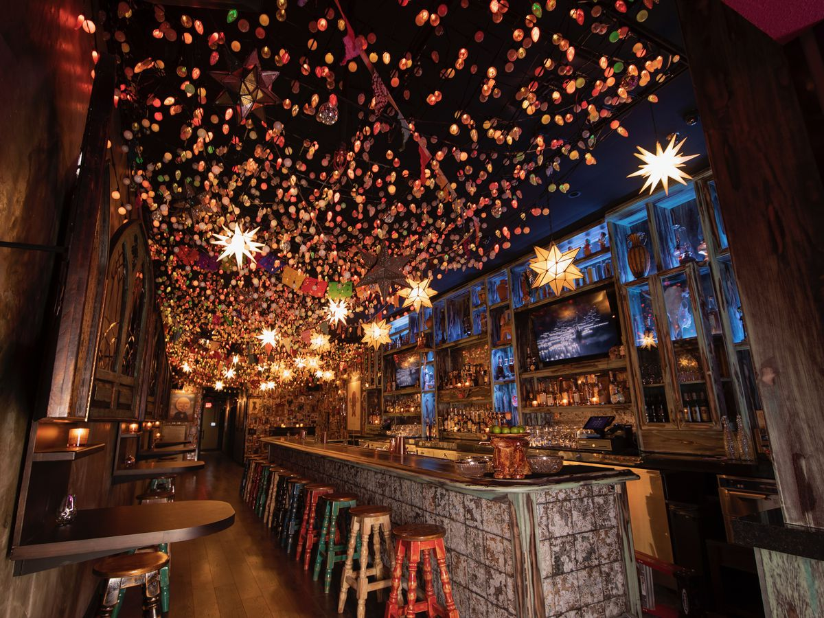 The inside of a bar with twinkle lights above and a bar on the right.