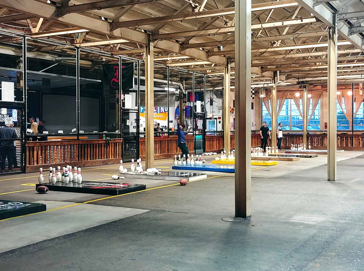 A large warehouse space with seven fowling lanes set up with pins and a bar with TVs beyond the game area