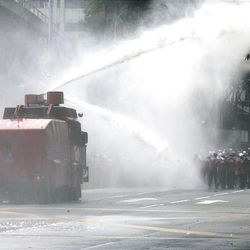 Protesters run as Police fire water cannon during an anti-Internal Security Act (ISA) demonstration in downtown Kuala Lumpur, Saturday.