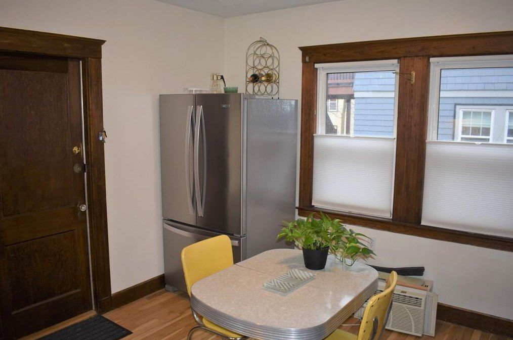 The corner of a kitchen, with a table and two chairs and a fridge in the corner.