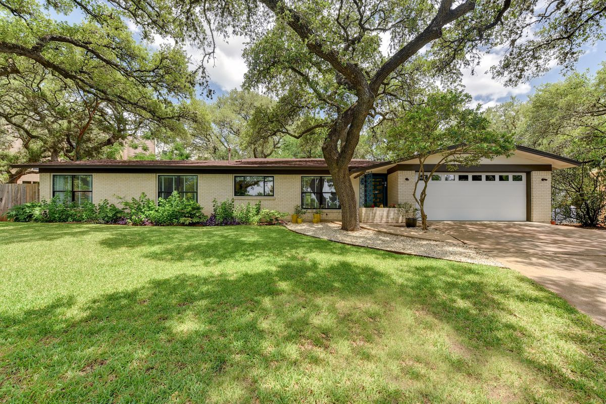 1960 tan brick ranch house with big oak in front