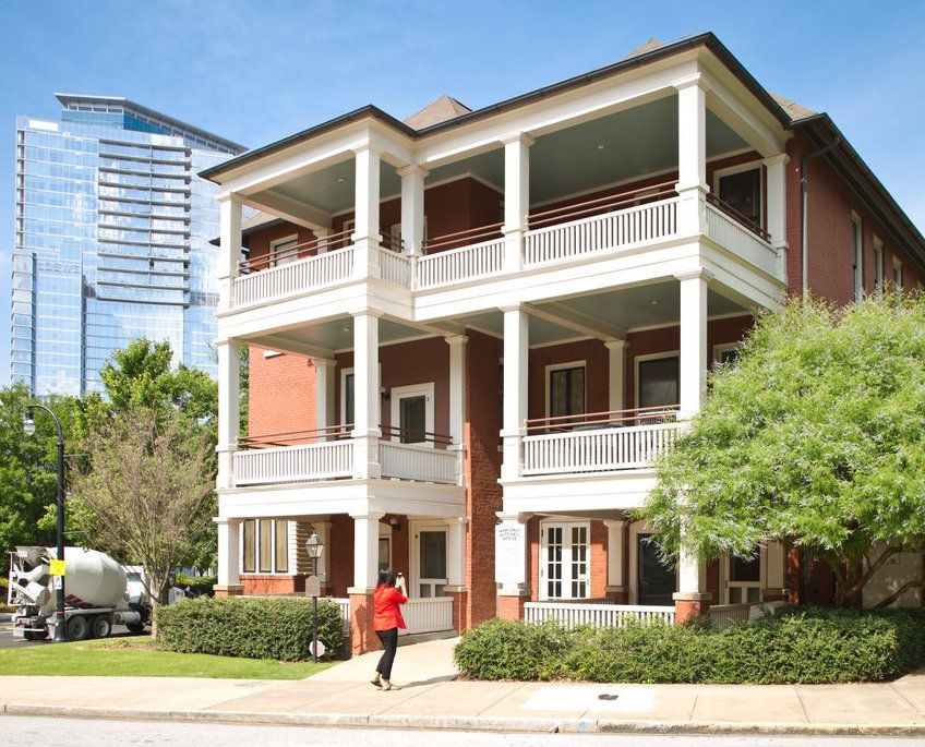 The exterior of the Margaret Mitchell House in Atlanta. The facade is red brick with white columns and railed in balconies on each level.