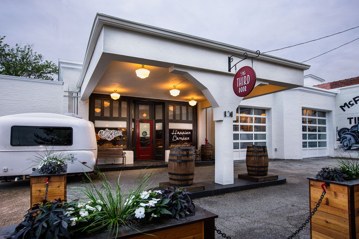 A white retro camper beside a bright white portico with large dark wood double doors at a bar in Marietta, GA, once an old gas station with two bourbon barrels where the gas pumps would be and a red sign hanging overhead with the name The Third Door
