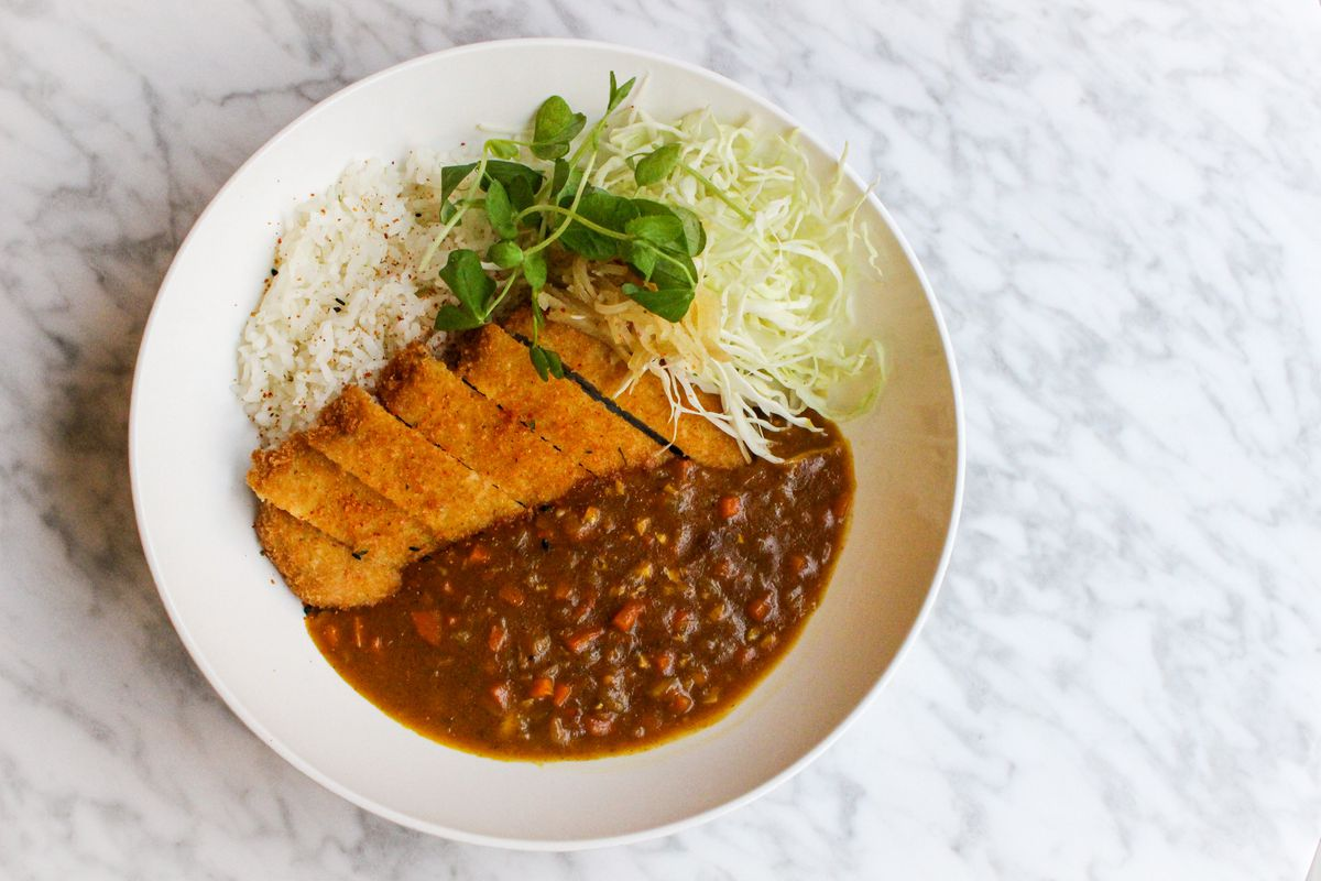 Deep fried pork cutlet plated with rice, cabbage, and Japanese curry