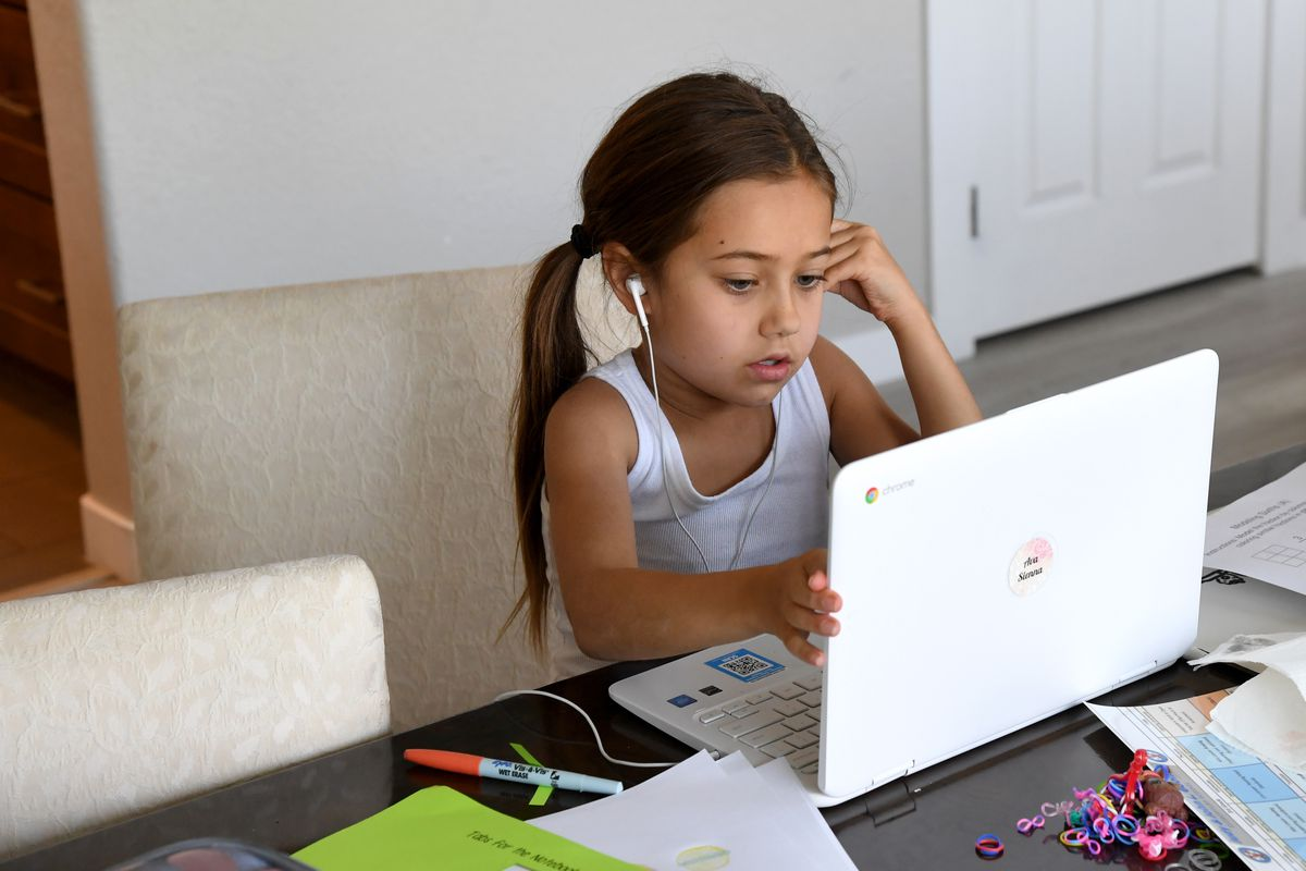 A nine-year-old girl takes an online class at a friend's home during the first week of distance learning for Nevada's Clark County School District.