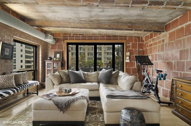 A living room in a former industrial space with rough, textured walls and large windows.