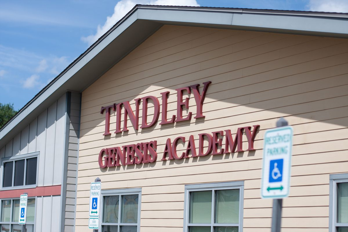 """The exterior of a building with yellow siding reads """"Tindley Genesis Academy"""" in big red letters."""