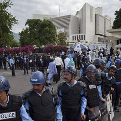 Policemen in riot-gears cordon off the Supreme court as Pakistani Prime Minister Yousuf Raza Gilani, unseen, appears for a hearing in Islamabad, Pakistan, Thursday, April 26, 2012. The Supreme Court convicted Gilani of contempt on Thursday for refusing to reopen an old corruption case against President Asif Ali Zardari on Thursday, but spared him a prison term in a case that has stoked political tensions in the country. (AP Photo/B.K. Bangash)