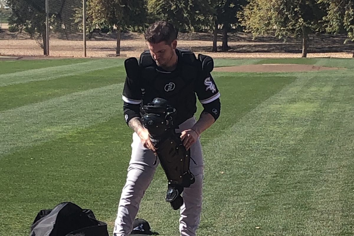 White Sox catcher Yasmani Grandal takes off his gear after catching pitchers' sidelines on the first day of spring training Wednesday.