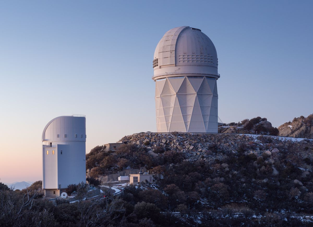 The exterior of the Kitt Peak National Observatory in Arizona. There are two white dome shaped structures. Each structure is positioned at the edge of a cliff. There is a sunset in the sky.