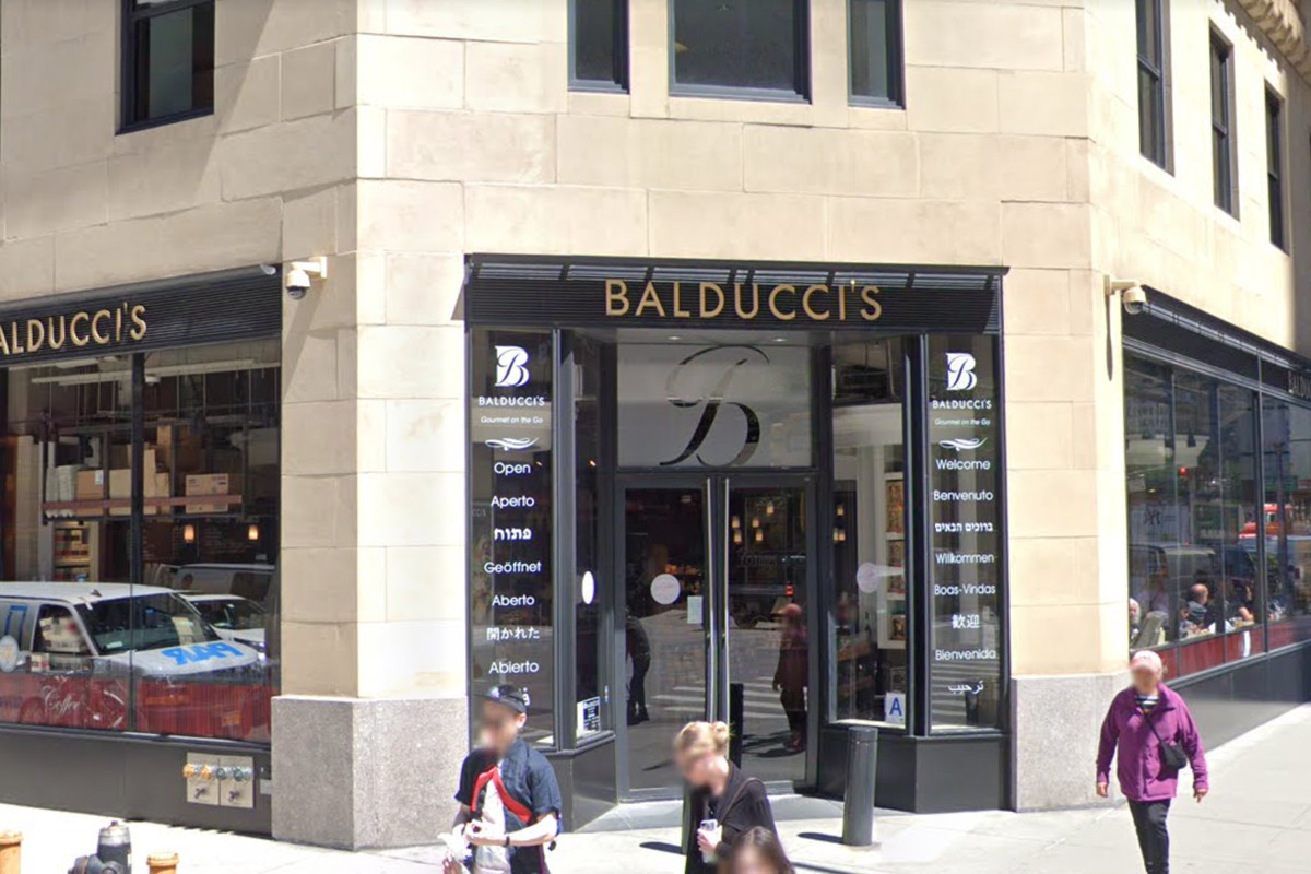 The exterior of a shop that reads Balducci's and people are walking along the sidewalk