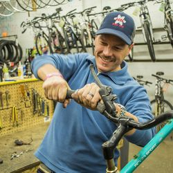 A man works on fixing the handlebar of a bike at one of the Bicycle Collectives.