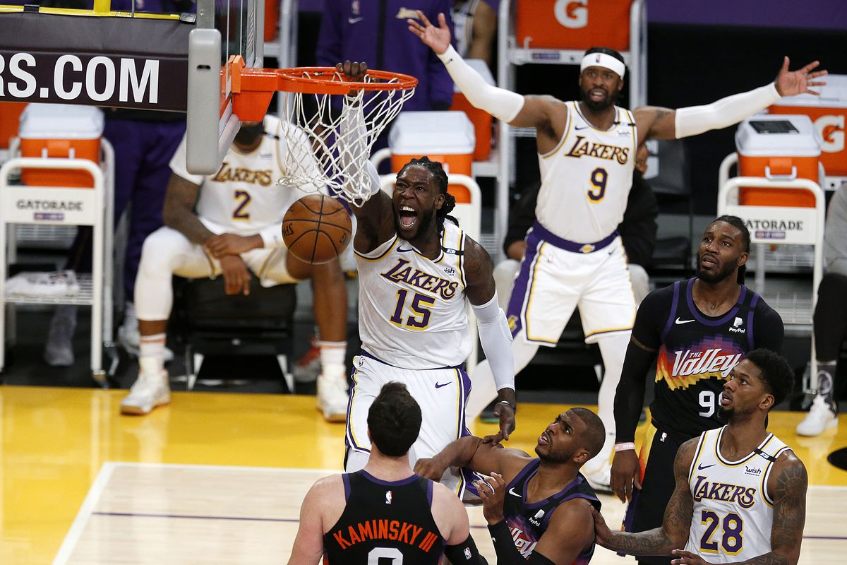 Los Angeles Lakers center Montrezl Harrell slam dunks the ball guarded by Phoenix Suns guard Chris Paul and Phoenix Suns forward Frank Kaminsky in the fourth quarter at the Staples Center on Sunday, May 9, 2021 in Los Angeles, CA.