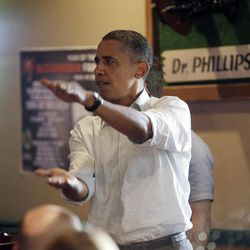 President Barack Obama does the 'Gator Chomp' as he walks into Gator's Dockside to greet patrons during an unschedule stop, Saturday, Sept. 8, 2012, in Orlando, Fla.