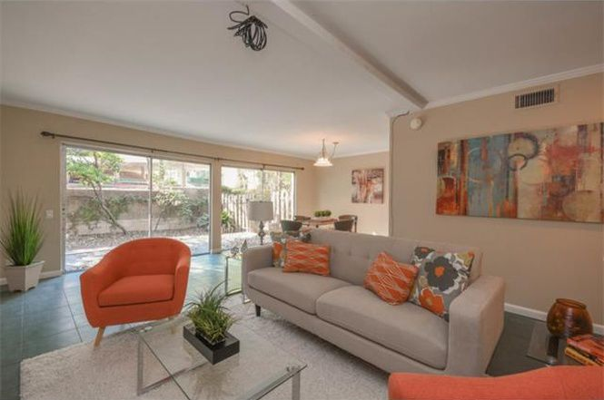 Condo living room with sliding glass doors, neitral furniture withp ops of orange, light blue/slate-colored lite floor