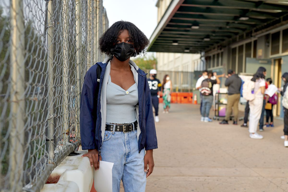 A young woman with curly hair and a protective mask stands outside of her high school on their first day.