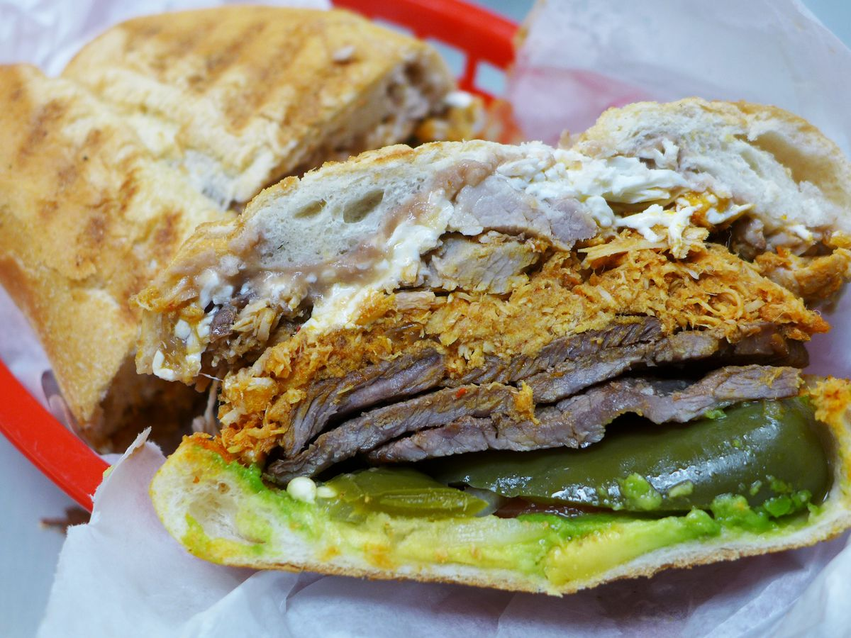 The Mexican sandwich called the torta, loaded down with multiple meats, string cheese, avocado, jalapenos, and many more ingredients.