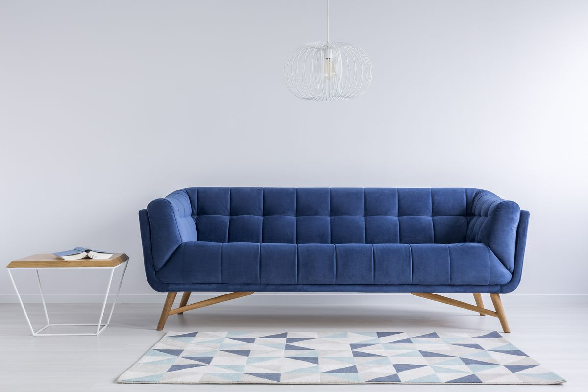 A royal blue couch in a white room with a patterned rug at its feet and a small, modern table to its left.