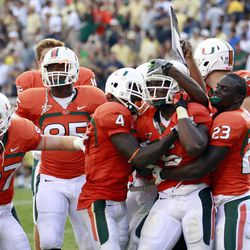 Miami running back Mike James (5) is mobbed by teammates Phillip Dorsett (4) and Eduardo Clements (23) after scoring the game-winning touchdown in overtime of an NCAA college football game against the Georgia Tech in Atlanta on Saturday, Sept. 22, 2012.