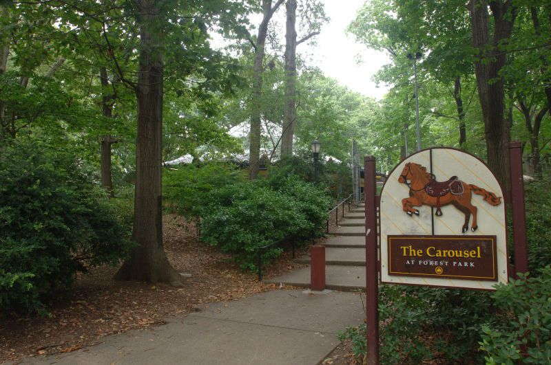 A park path surrounded by trees. There is a sign on the path that reads The Carousel at Forest Park.