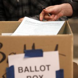 Voters place ballots in boxes at a Democratic caucus at Emerson Elementary School in Salt Lake City on Tuesday, March 22, 2016. The location ran out of ballots and had to print more on site.