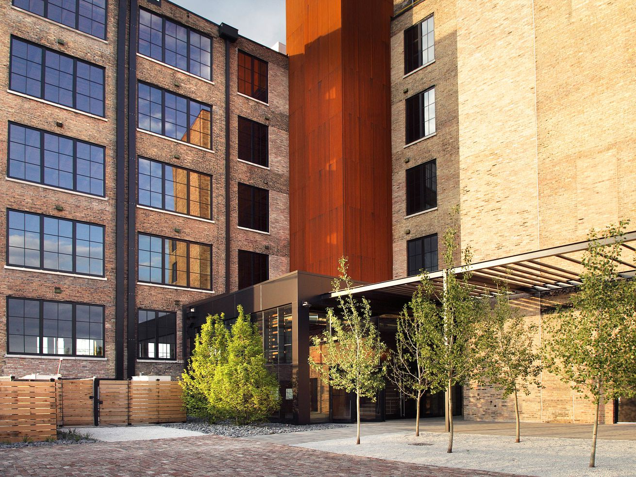 The building's former loading dock now serves as a landscaped courtyard leading to the lobby. A new elevator shaft is clad in corten steel.