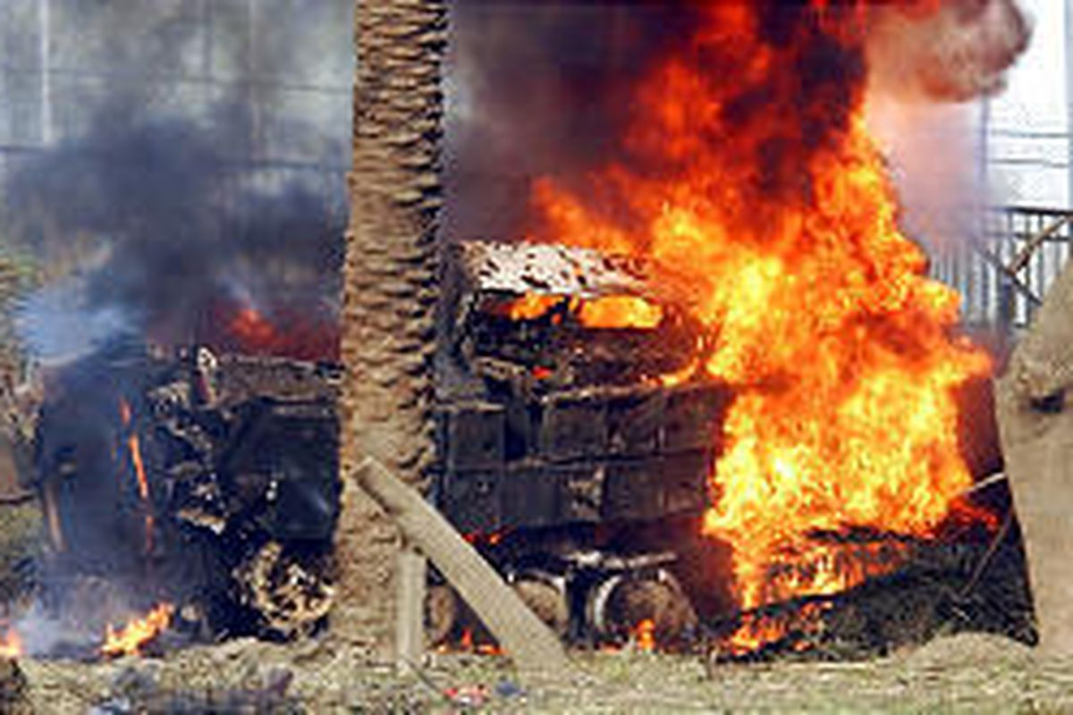 A U.S. Army armored vehicle burns on the airport highway in Baghdad. A roadside bomb exploded near convoy, injuring six soldiers.