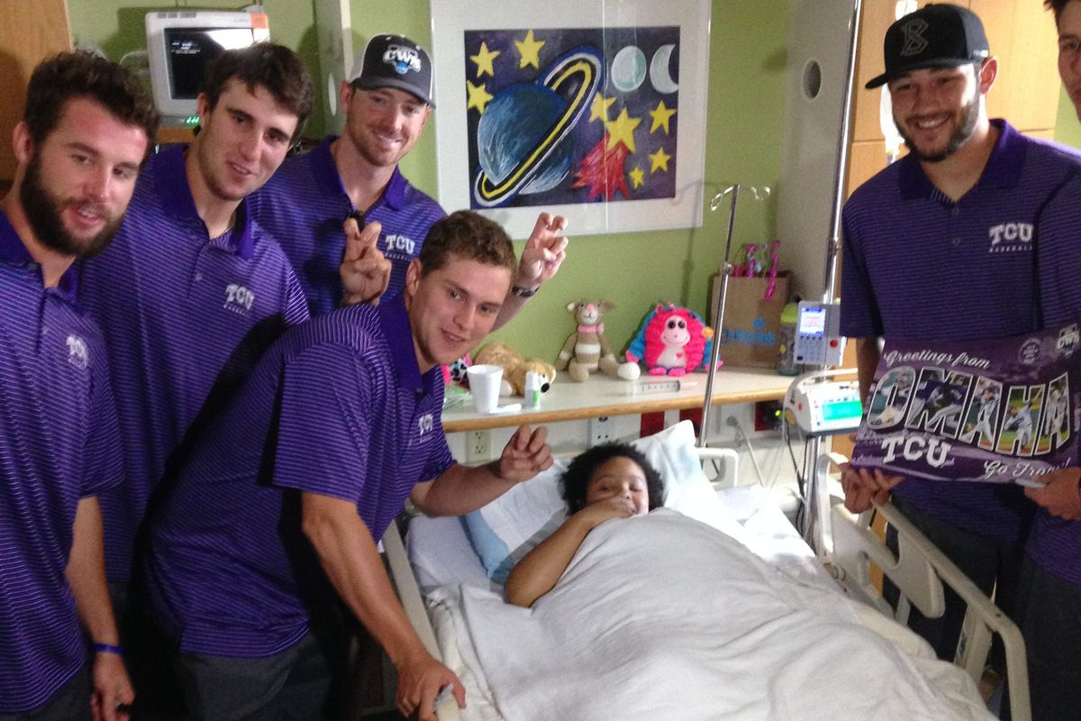TCU players flash the Horned Frog sign with Markeva, a 14-year-old patient