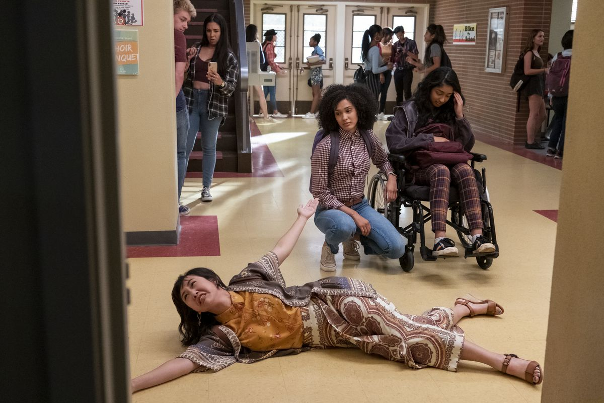 Ramona Young flops on the floor in the school hallway as Lee Rodriguez and Maitreyi Ramakrishnan look on in Never Have I Ever