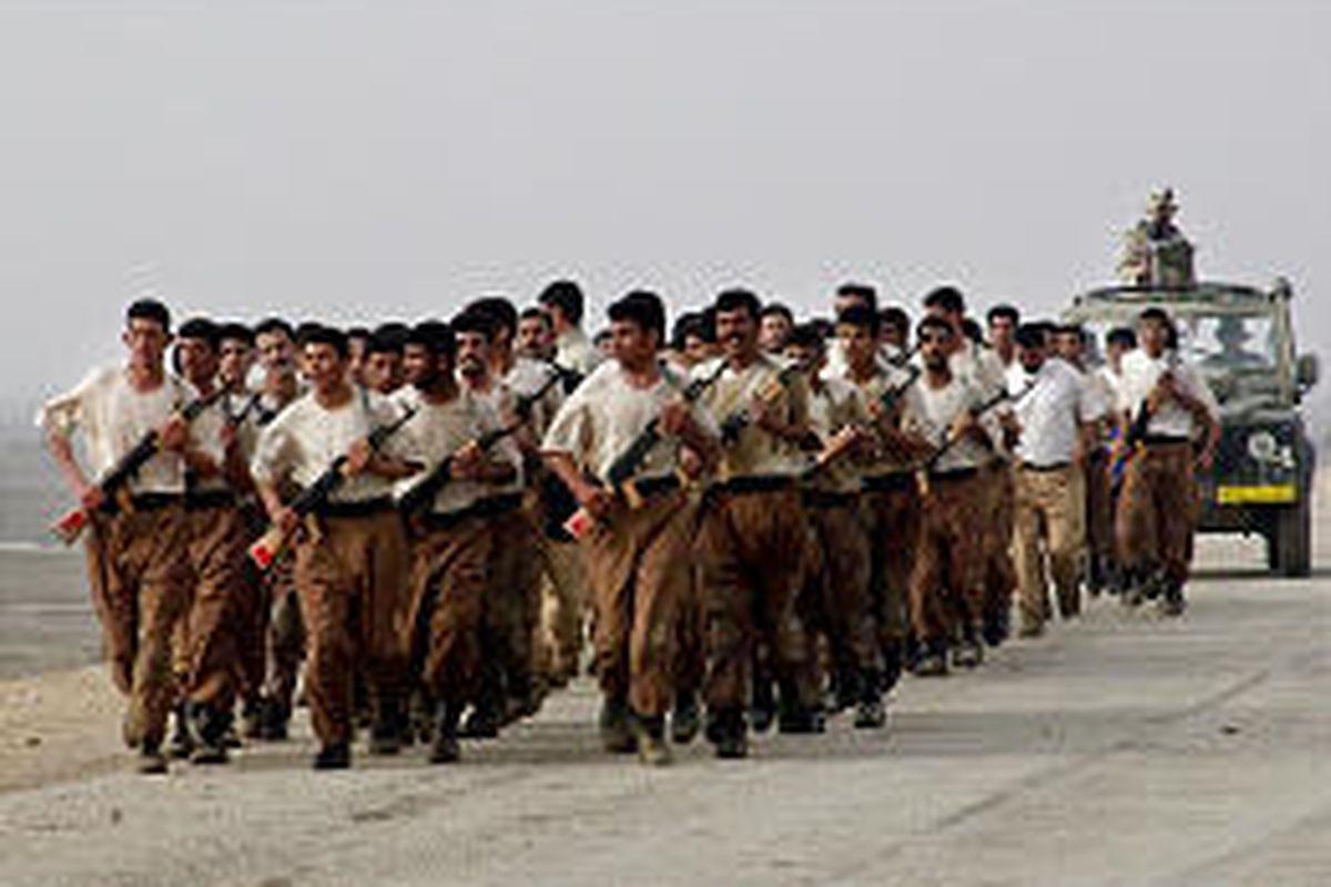 New Iraqi army recruits jog near Samawa, Iraq, as Dutch troops drive behind as escorts in January 2004.