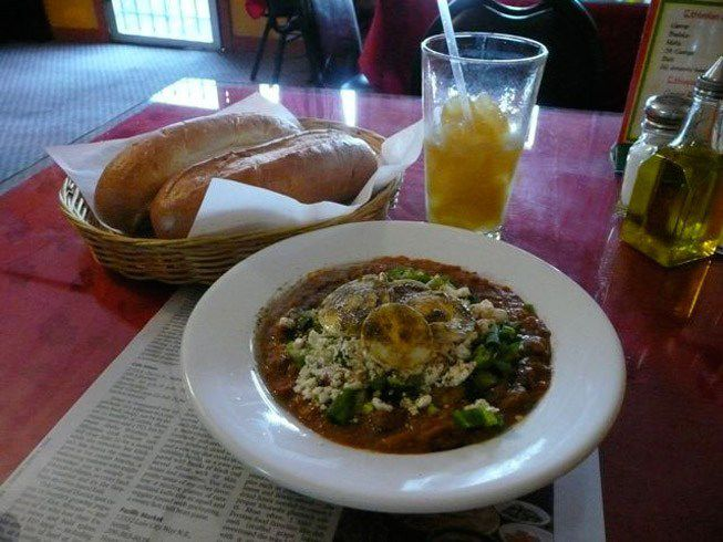 A bowl of Ethiopian food with a basket of bread off to the side and a half-empty glass of iced tea