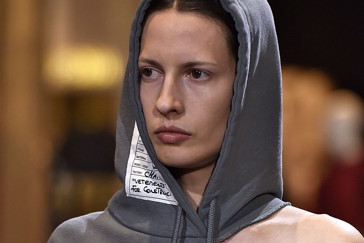 A model walks the runway wearing a gray hoodie that has been torn at the seam of the hood to reveal a slice of shoulder.