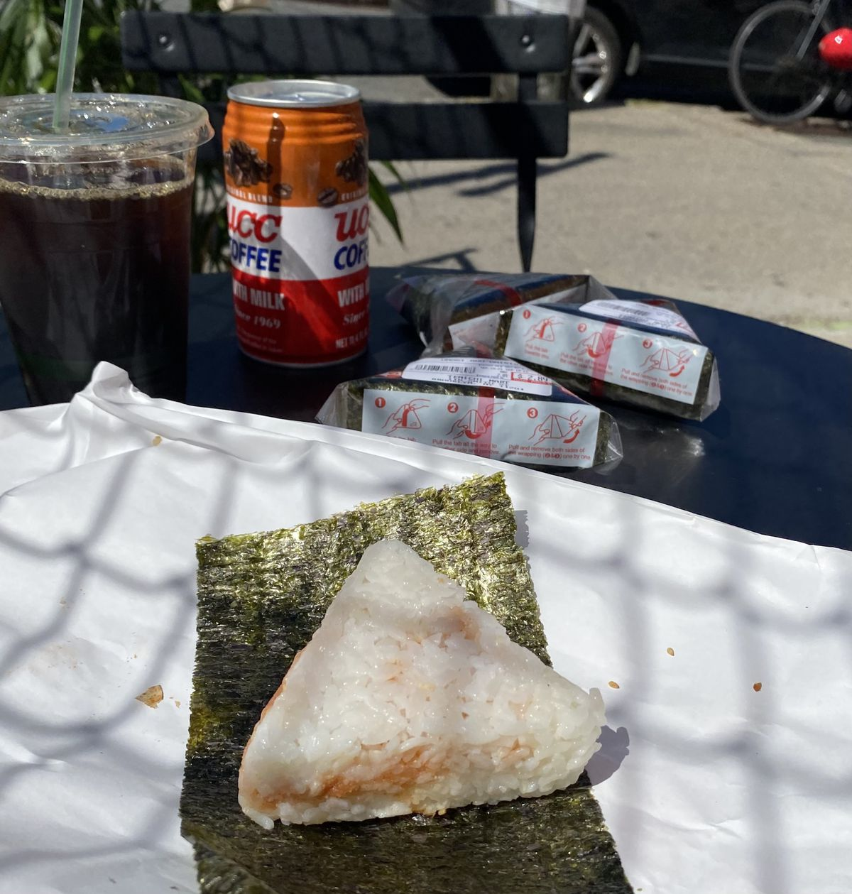A triangular piece of onigiri rests on a piece of seaweed on a paper bag. In the background, three additional onigiri sit beside an iced coffee.