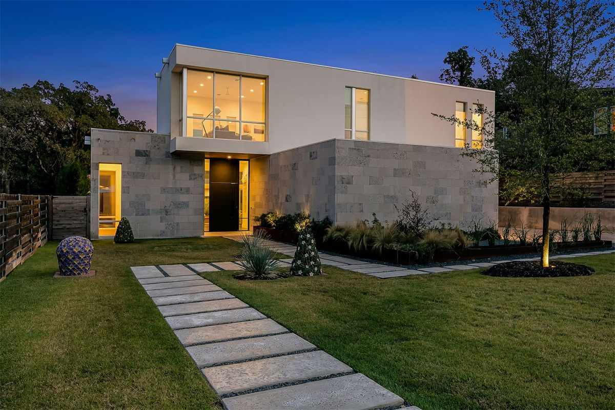 Blocky stucco-and-concrete home with lawn in from