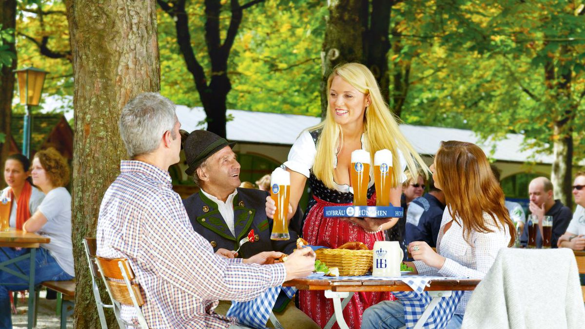 A server dropping off beer to a table of three.