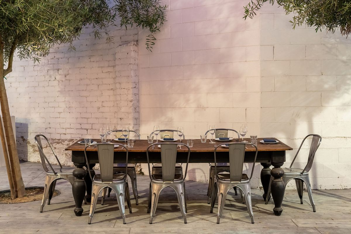A small family-style outdoor table for dining at a restaurant.
