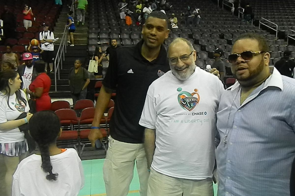 New York Knicks Assistant to the President Allan Houston posing on the court with two fans after Sunday's win.