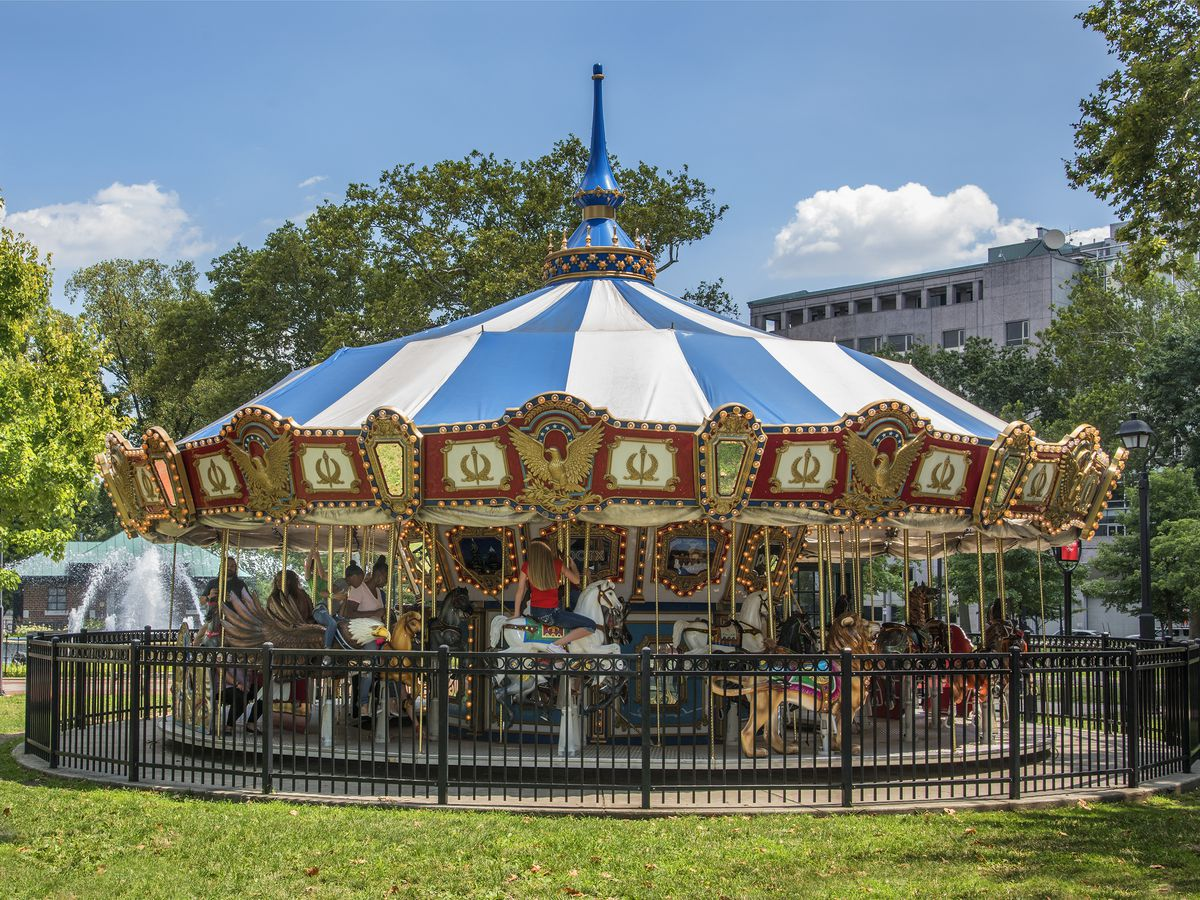 A carousel with a blue and white top is in Franklin Square, Philadelphia.