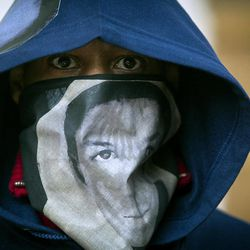 """A man wears a hoodie and a scarf with the likeness of Trayvon Martin during a """"One Thousand Hoodies March for Trayvon Martin"""" event Thursday, March 29, 2012 at the University of Minnesota campus in Minneapolis. Martin, a Florida teenager, was wearing a hoodie when he was shot and killed by a neighborhood watch volunteer."""