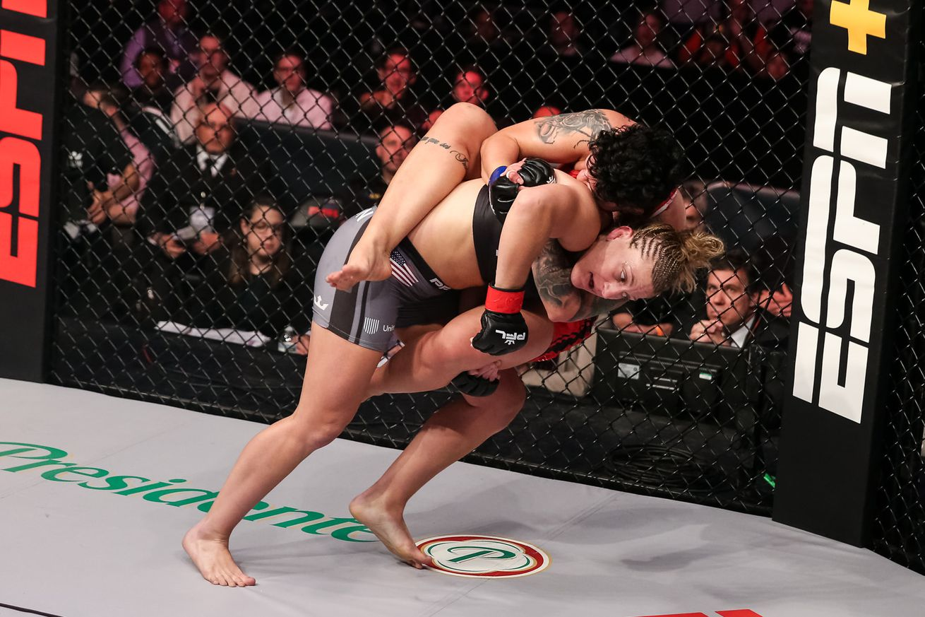Kayla Harrison (red gloves) tries to shake off Larissa Pacheco in the lightweight main event of PFL 12 in Uniondale, New York, on Thursday