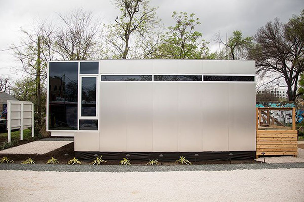 A sleek, small, mobile home with stainless metal siding, tinted windows, and small clerestory windows at the top.