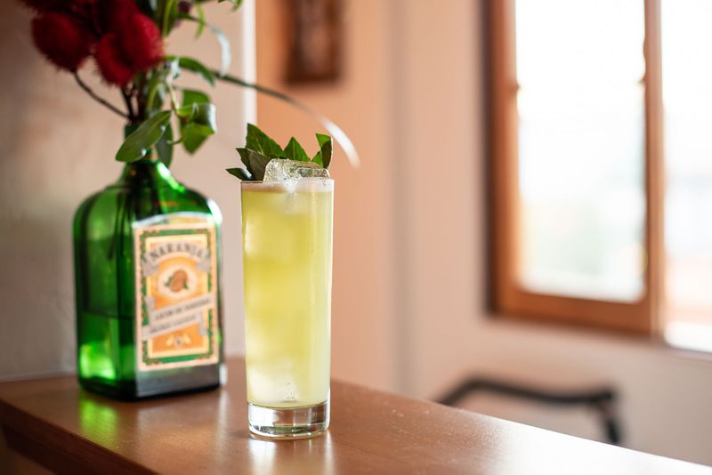 Light green cocktail with garnish on a counter with flowers in the background.