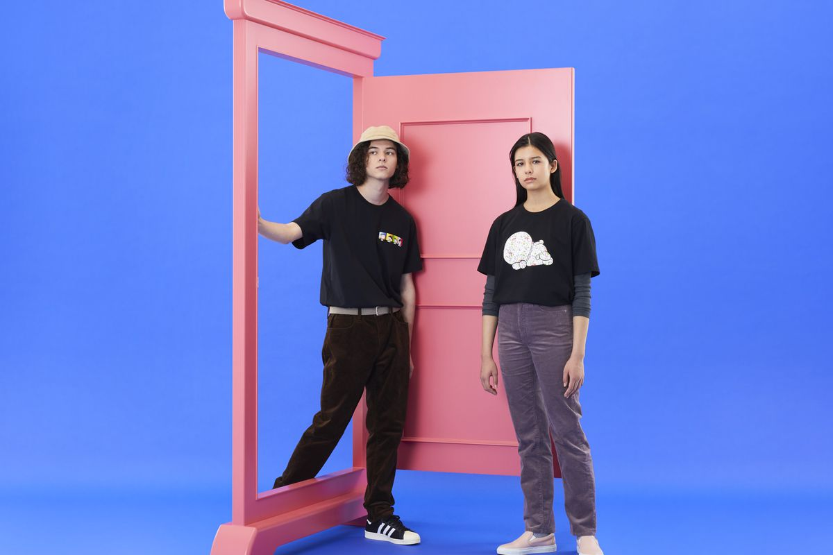 A young man and young woman walk through a pink door wearing shirts from Uniqlo's Doraemon collection