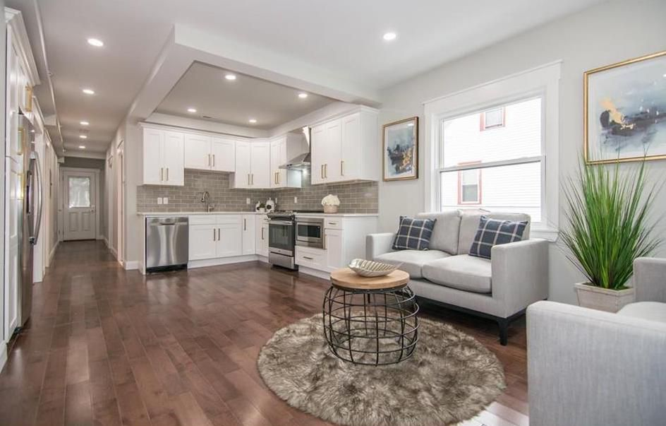 An open living room and kitchen with furniture and a long hallway to the front door off it.
