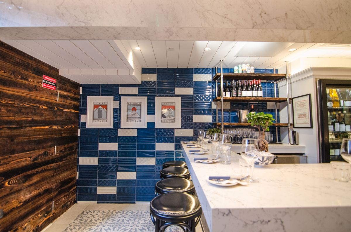 Shiny black stools line a white marble bar. In the background, there's a dark blue-tiled wall and another wall with dark wood. The floor is covered with Spanish-style tiles.