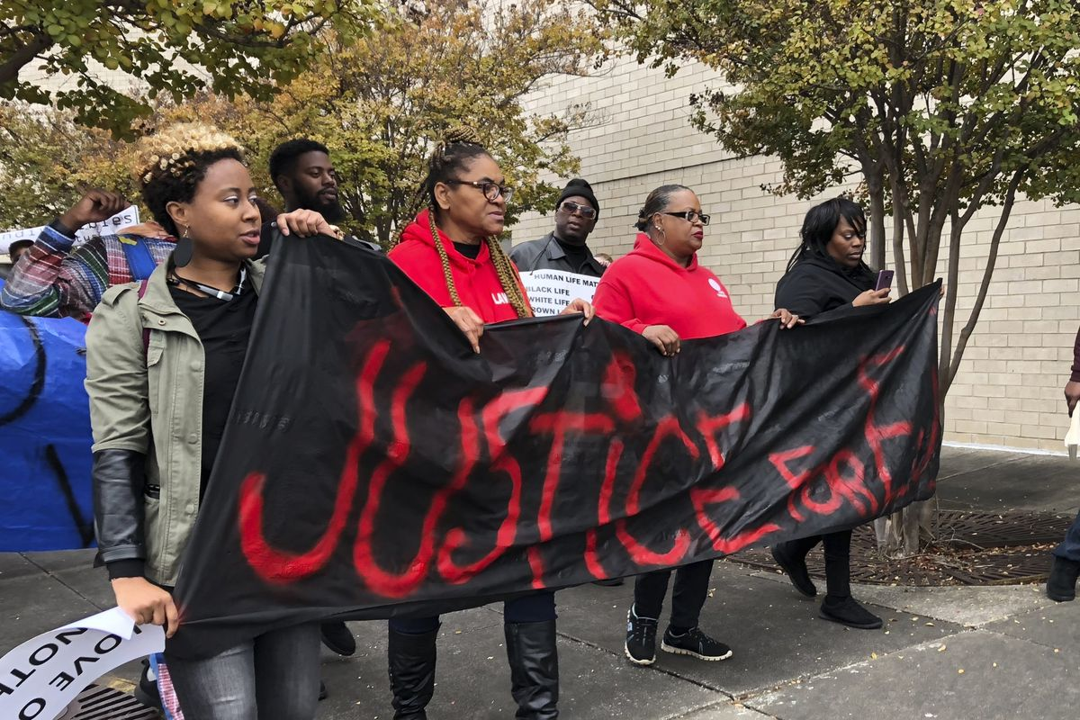 """Protesters in Alabama carry """"Justice for E.J."""" signs days after Emantic Bradford Jr. was killed by a police officer."""
