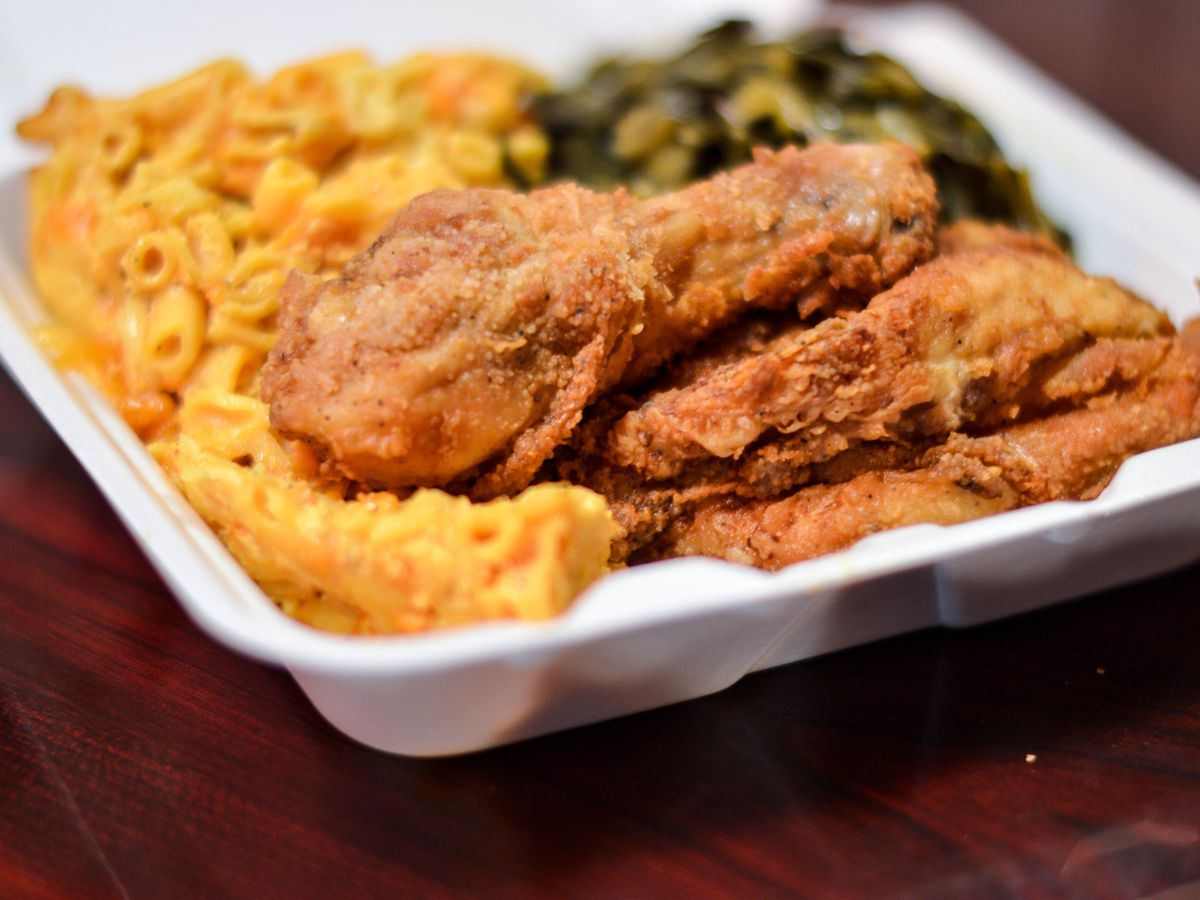 Fried chicken, mac and cheese, and collard greens in a styrofoam container