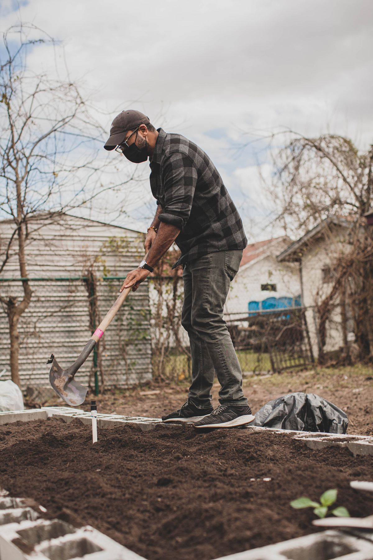 A man in a black-and-grey plaid shirt uses a shovel to spread soil in a raised garden bed