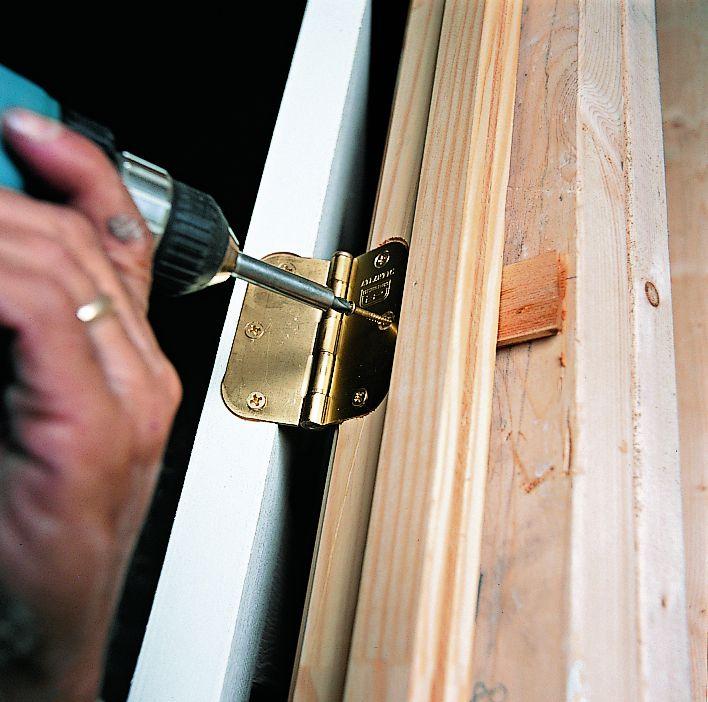 Man Removes Center Screw From Top Hinge Leaf Of Prehung Door